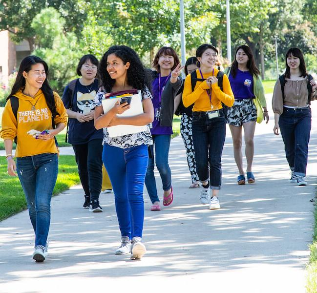 Group of diverse students walking on campus