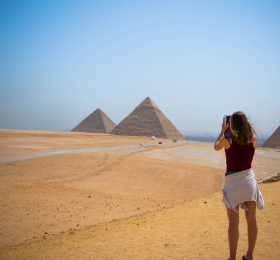 Woman taking a picture of pyramids in distance