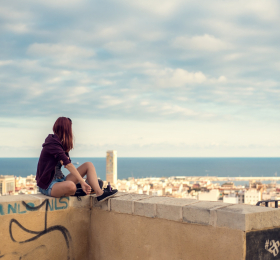 Student sitting on ledge overlooking a city scape