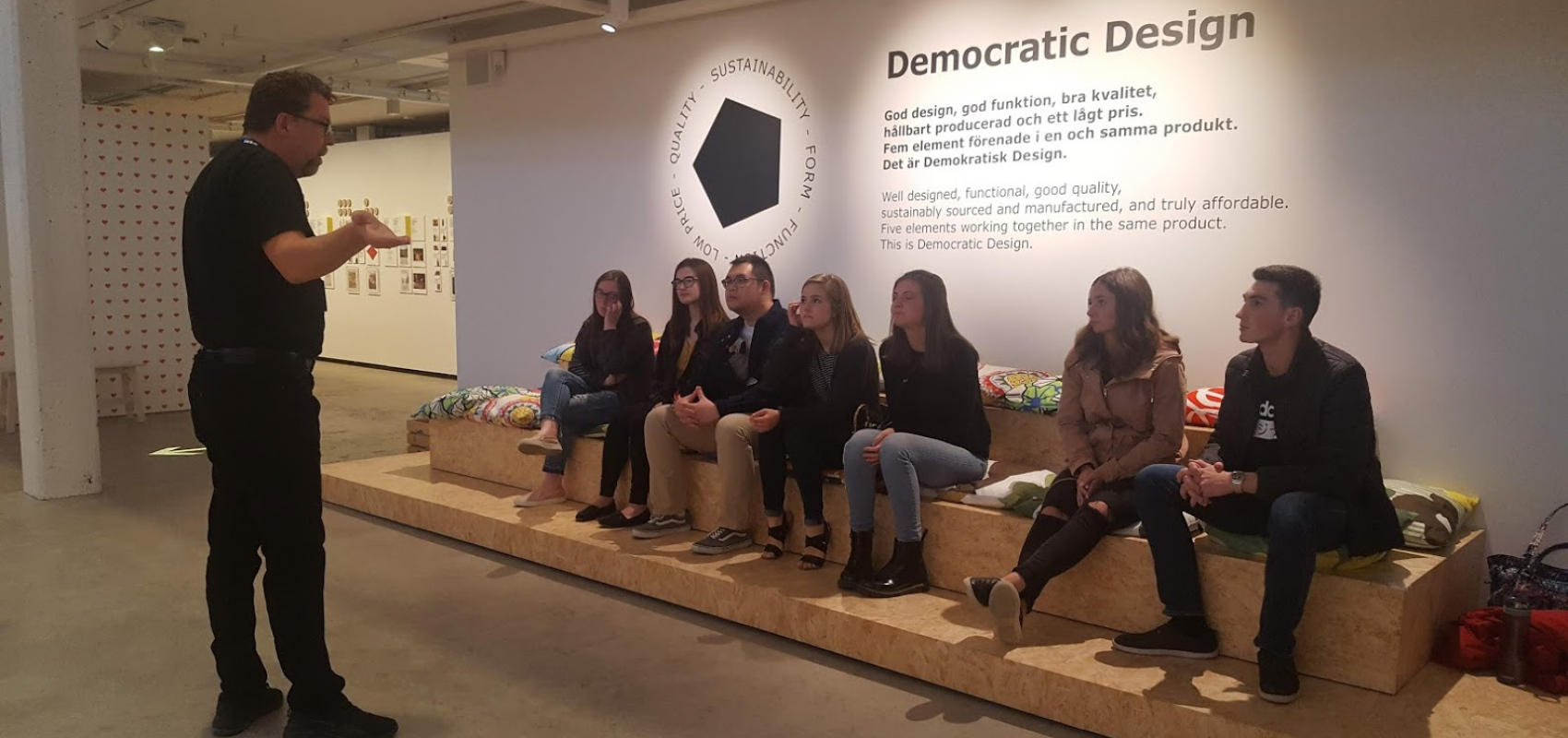 Group in front of a wall that explains democratic design