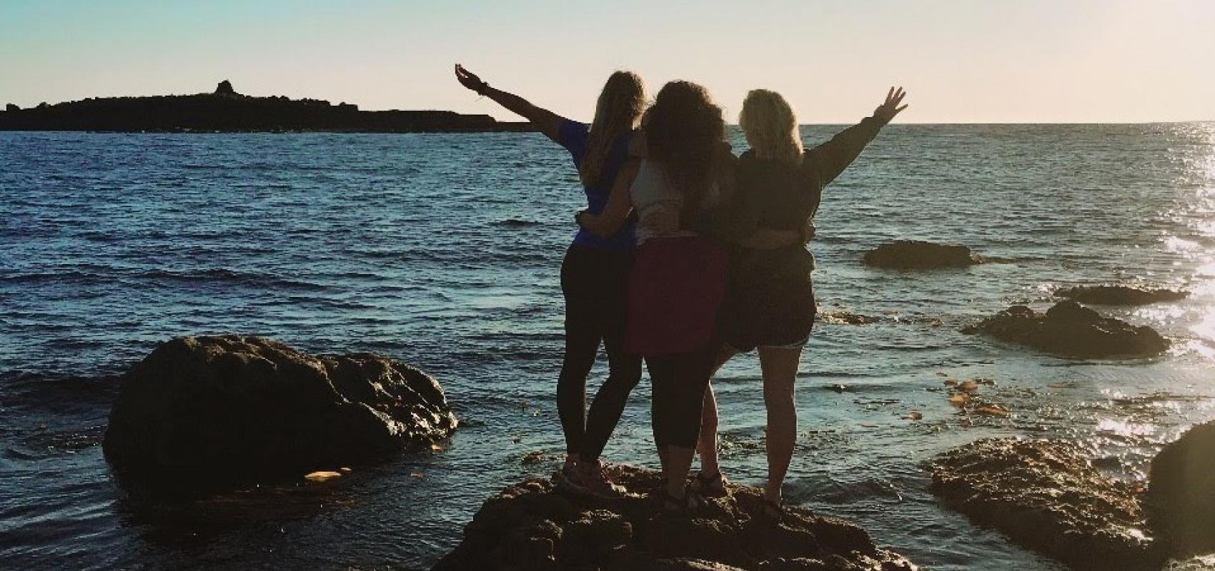 Students on coast at sunset