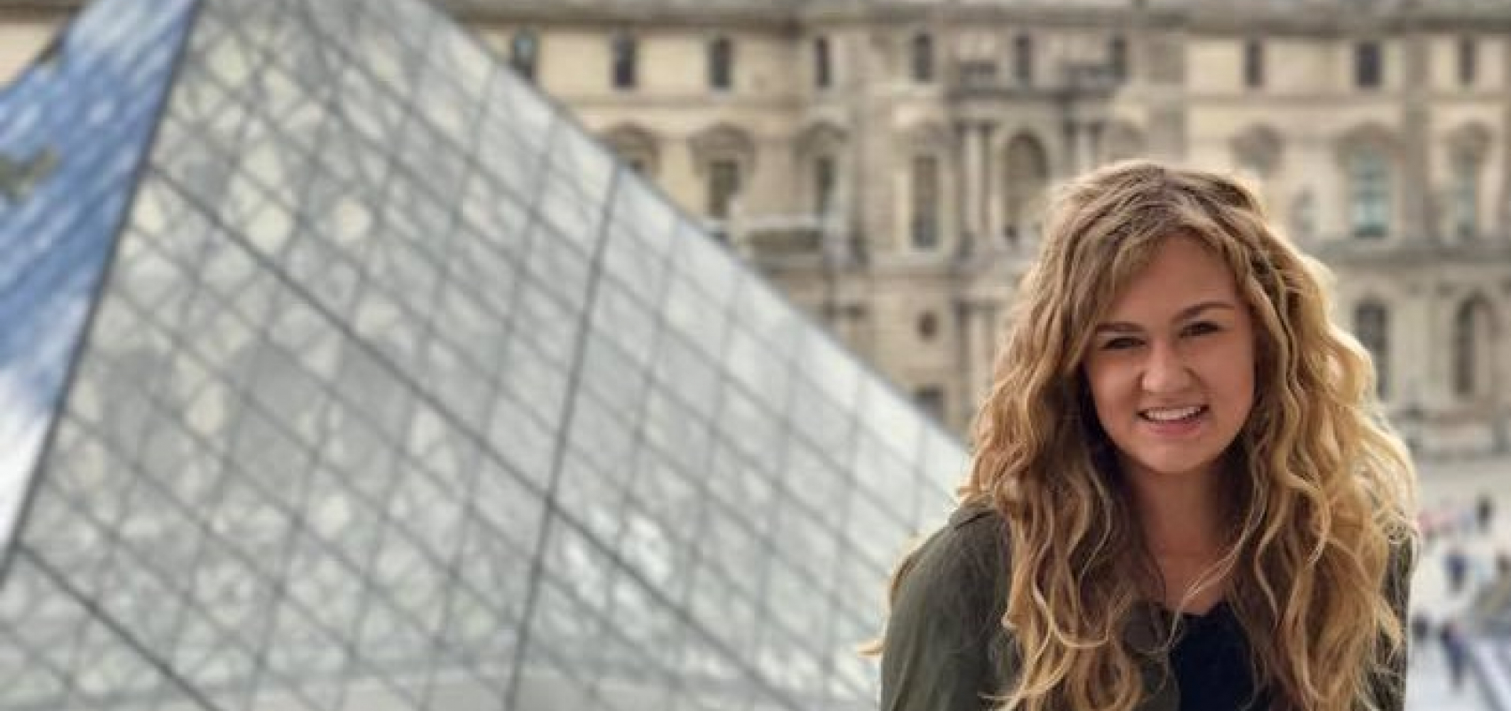 UNI student in front of glass pyramid of the Louvre