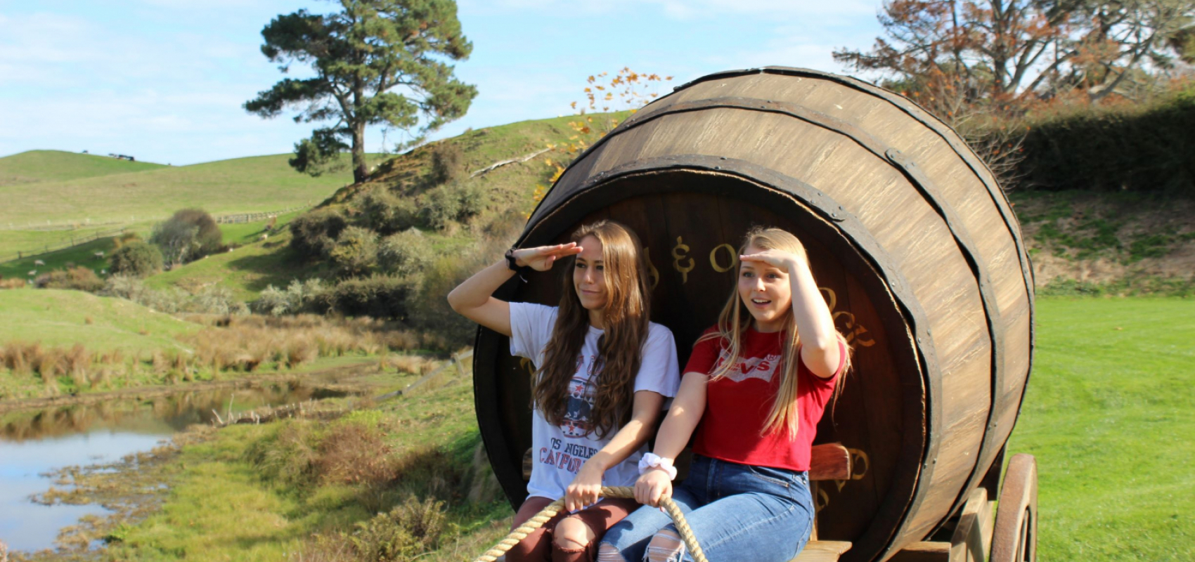 Two students riding on cart at Hobbiton