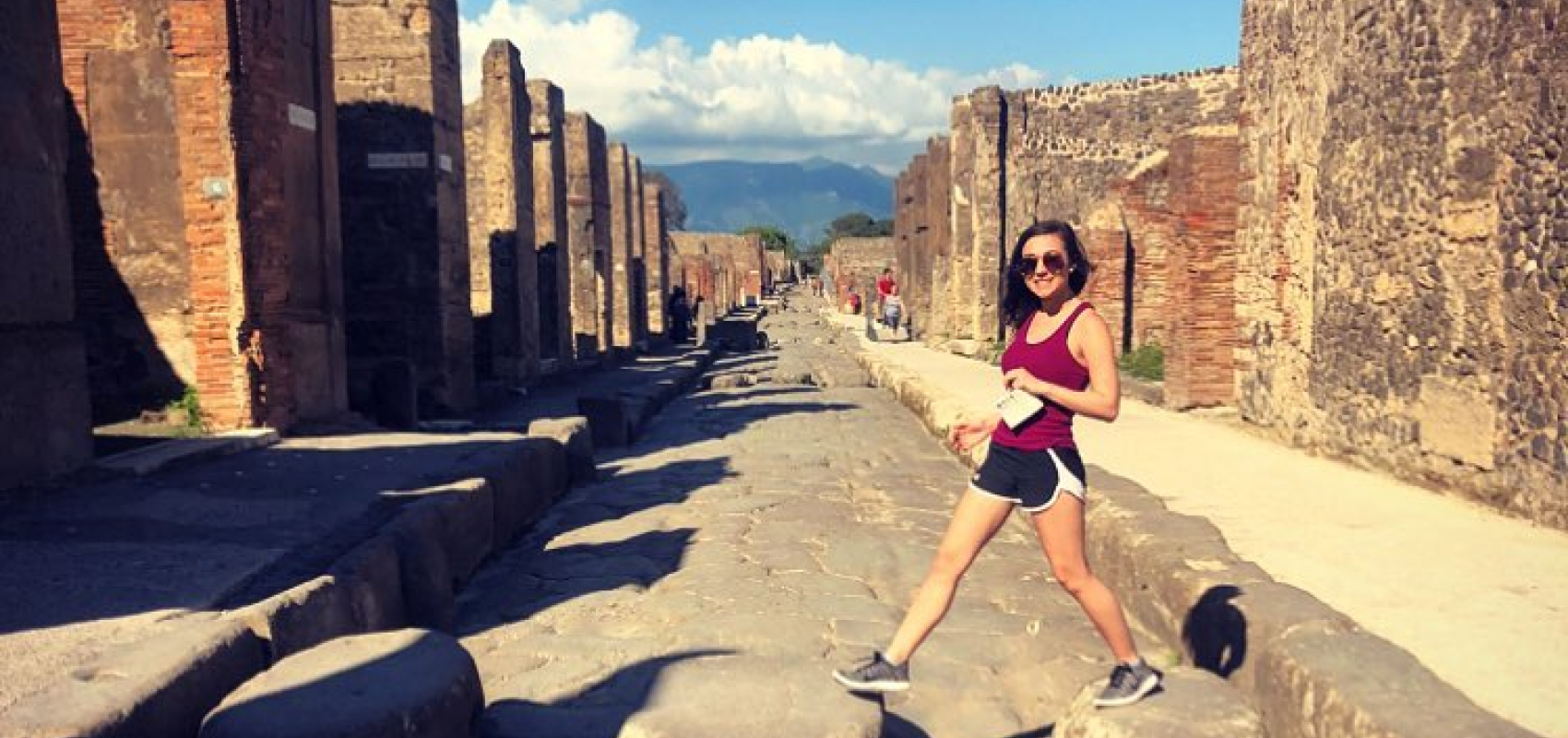 UNI student crossing ancient stone street at the ruins of Pompeii