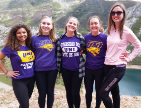 Five students standing by a lake
